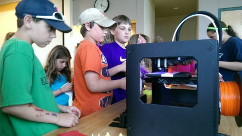 kids looking at 3d printer